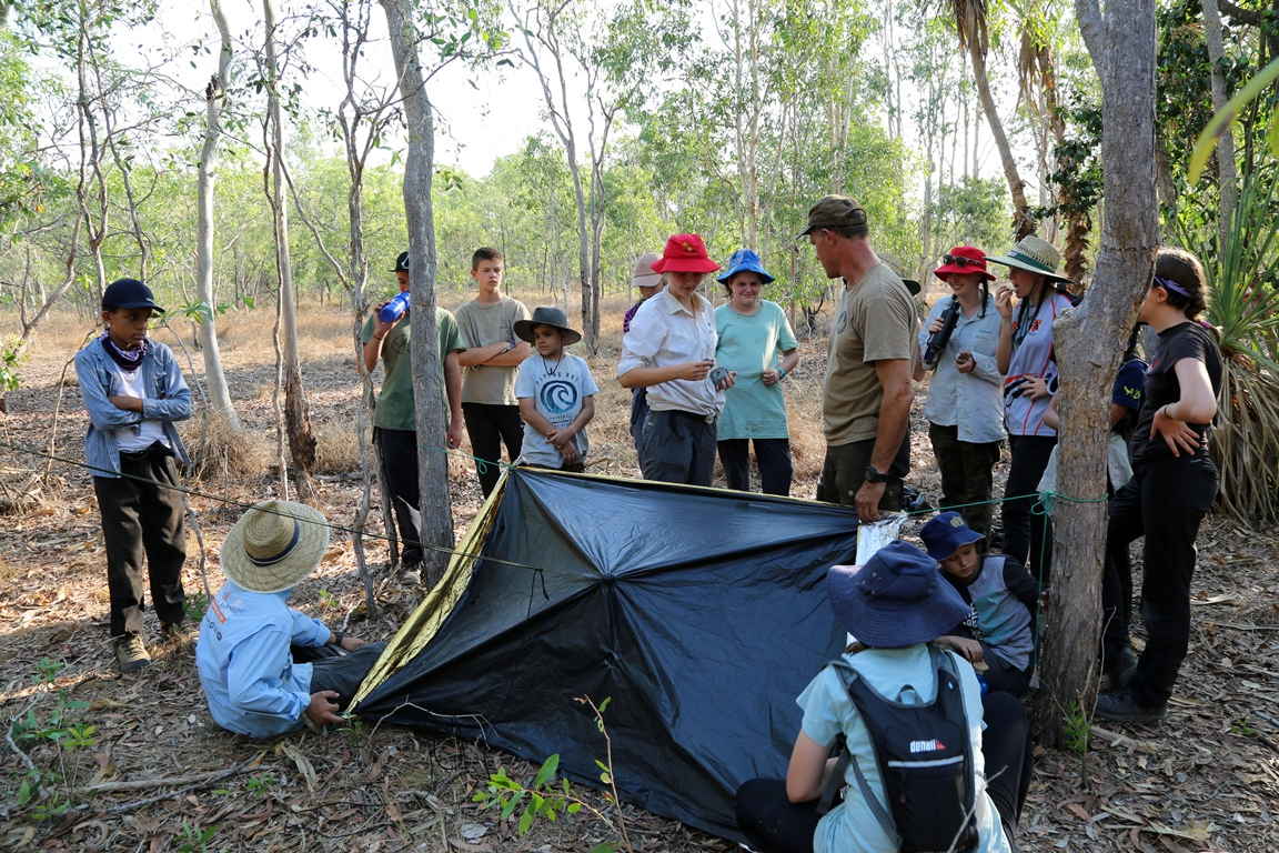 Learning how to erect an emergency shelter using a garbage bag