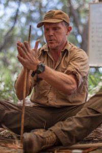Gordon using friction fire rubbing two sticks together