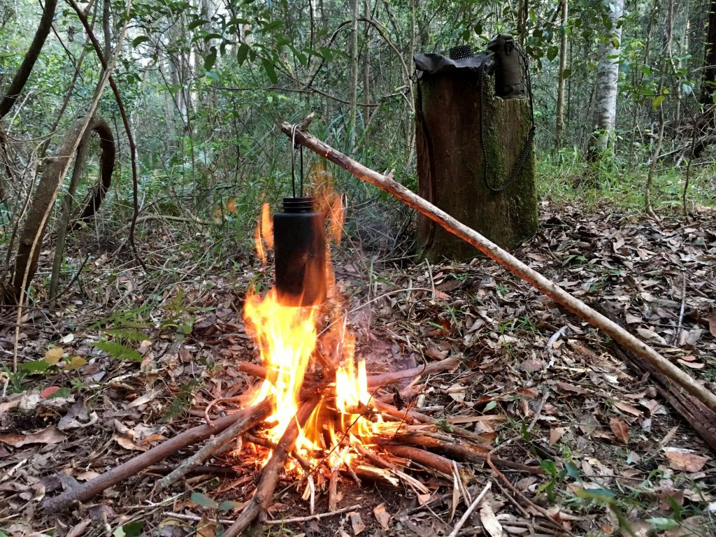 Cooking pot hanging over a small campfire in bush surrounds
