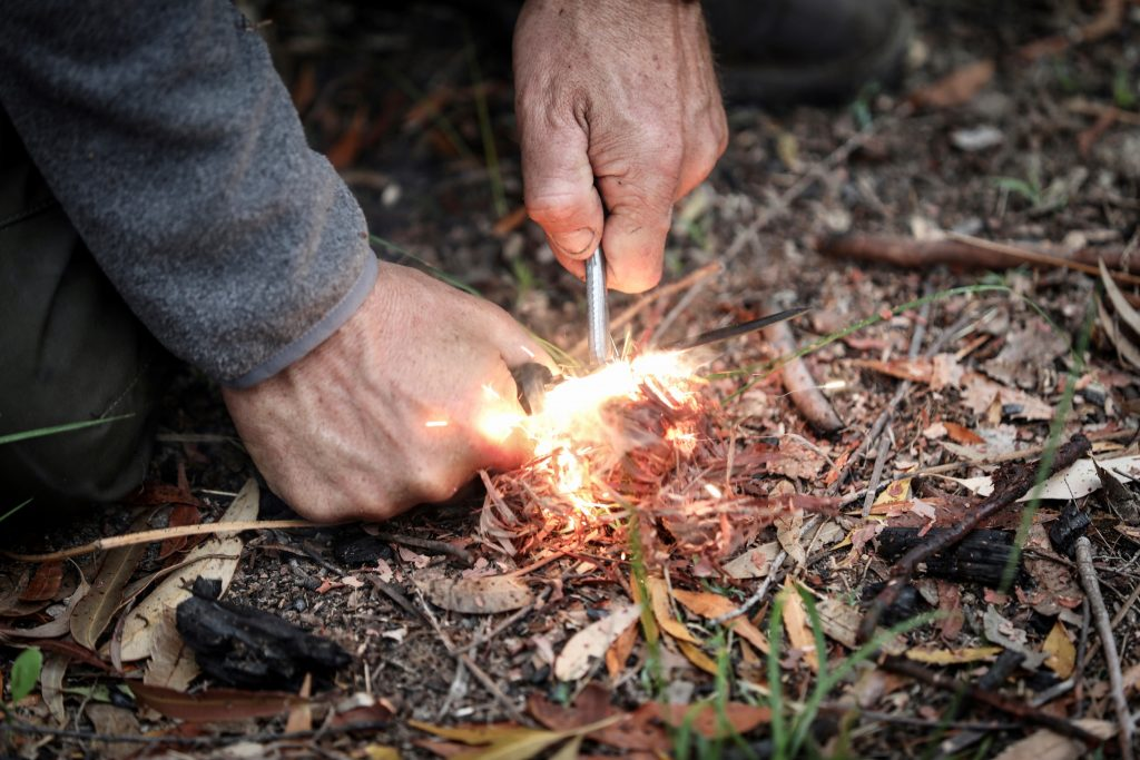 Man lighting tinder with sparks from a ferrocerium rod