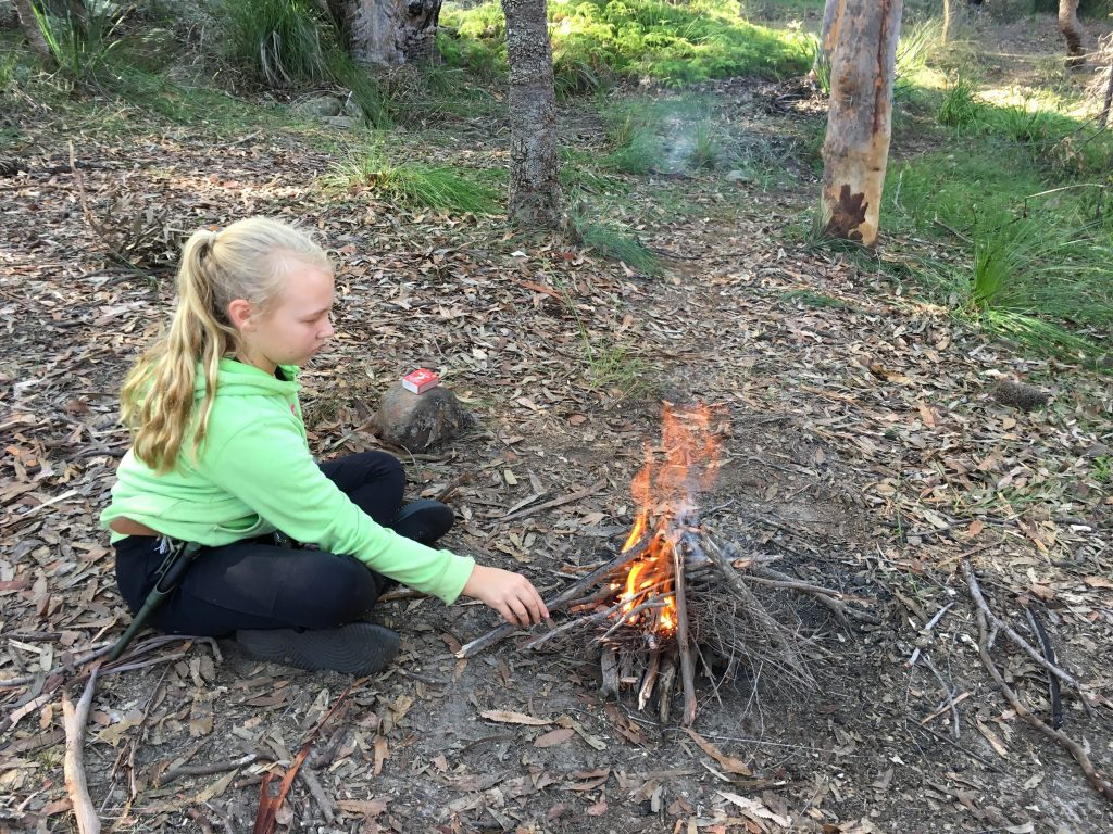 Young girl managing a small campfire in the bush